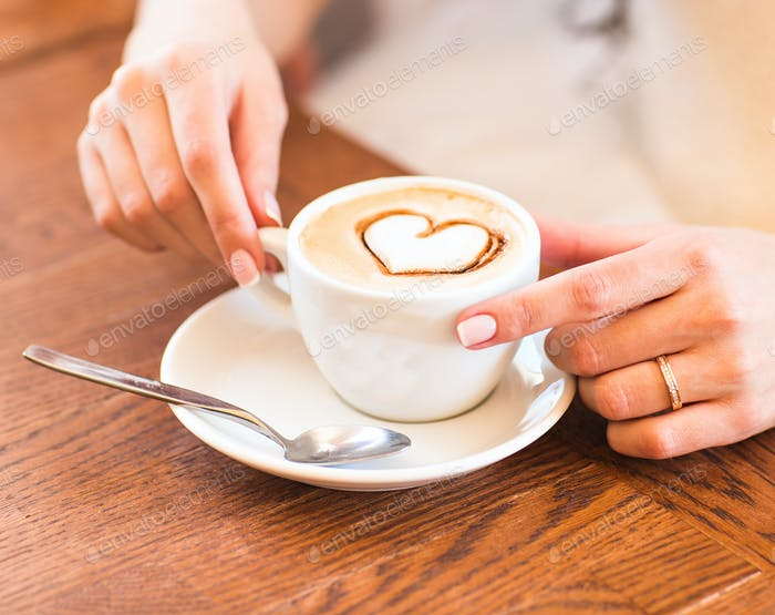 woman holding hot cup of coffee, with heart shape.
