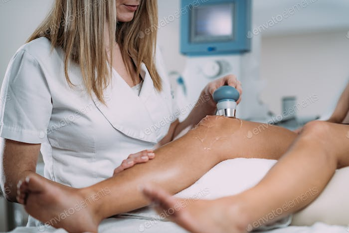 Ultrasound in Physical Therapy. Therapist Using Ultrasound Applicator on a Patient's knee
