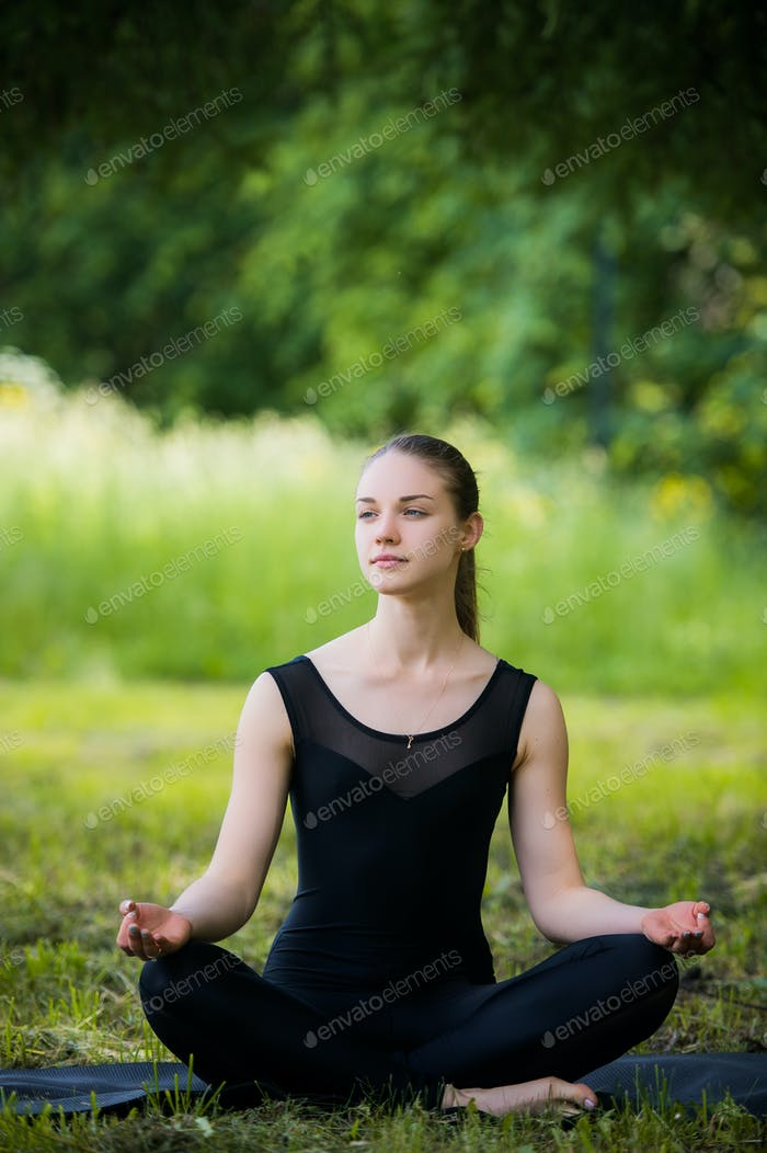 Beautiful young girl meditating in summer park