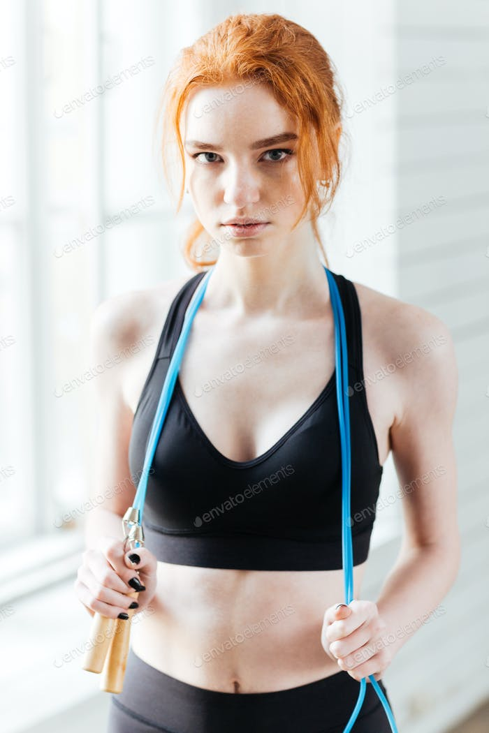 Fitness woman holding skipping rope at the gym