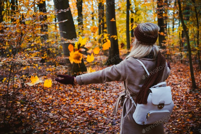 Woman throwing autumn leaves into the air. Carefree, happiness concept. Scenic fall park