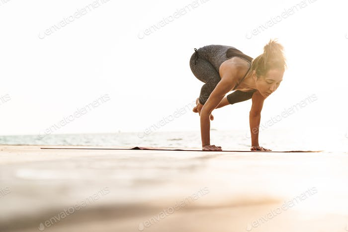 Photo of beautiful sportswoman handstanding while practicing yoga by seaside in morning