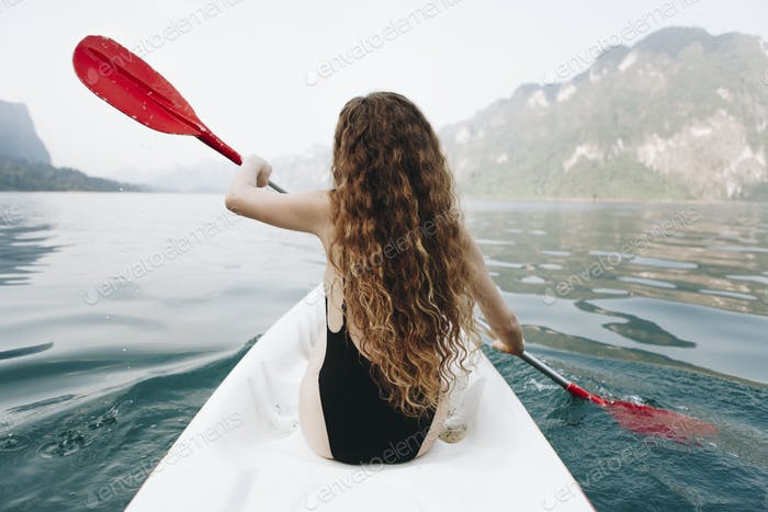 Woman paddling a canoe through a national park