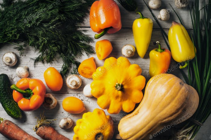 Yellow and green vegetables on the white wooden table horizontal