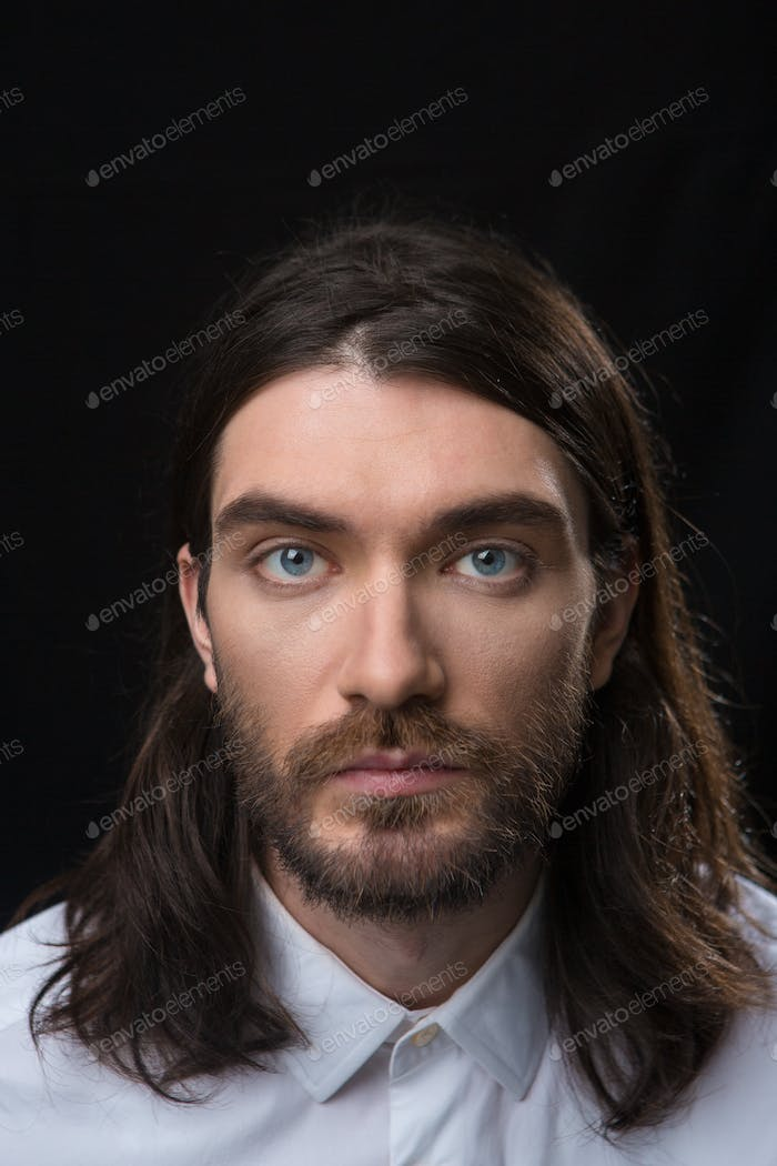 Man with beard and long hair looking at camera