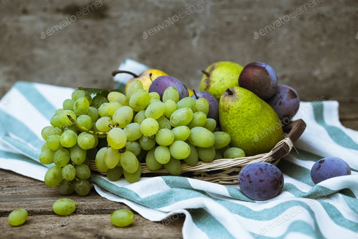 fruit grapes plum pear on wooden background