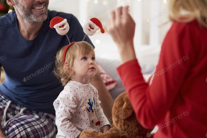 Happy baby with parents in Christmas morning