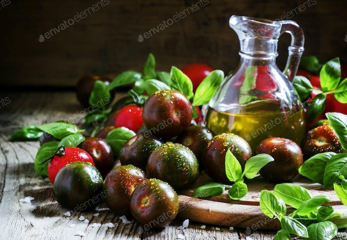 Dark green cherry tomatoes Black Prince, red tomatoes, fresh green basil