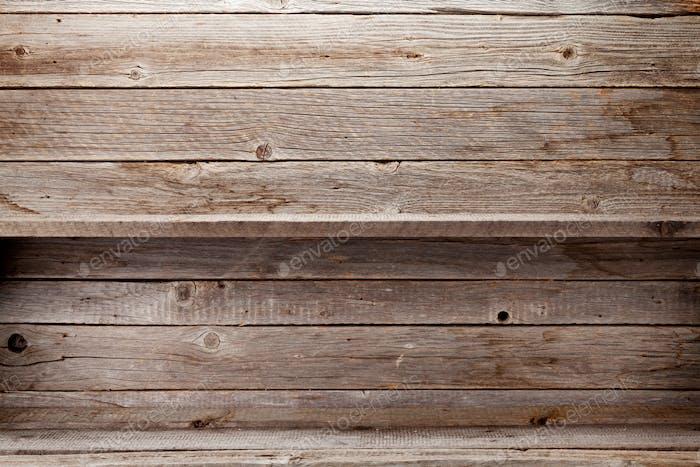 Leere Holzregale vor der Holzwand