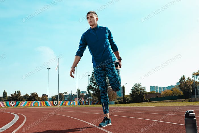 Man runner stretching legs preparing for run training on stadium tracks doing warm-up