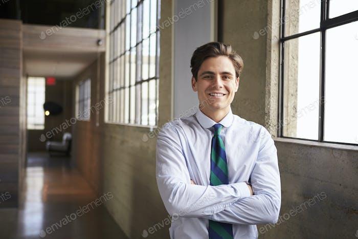 Junge weiße Geschäftsmann steht lächelnd mit Armen gekreuzt