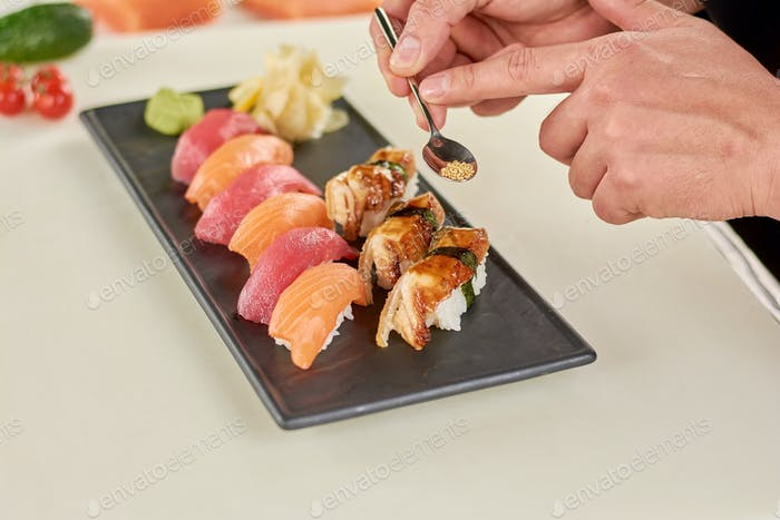 Chef holding spoon with sesame for sushi