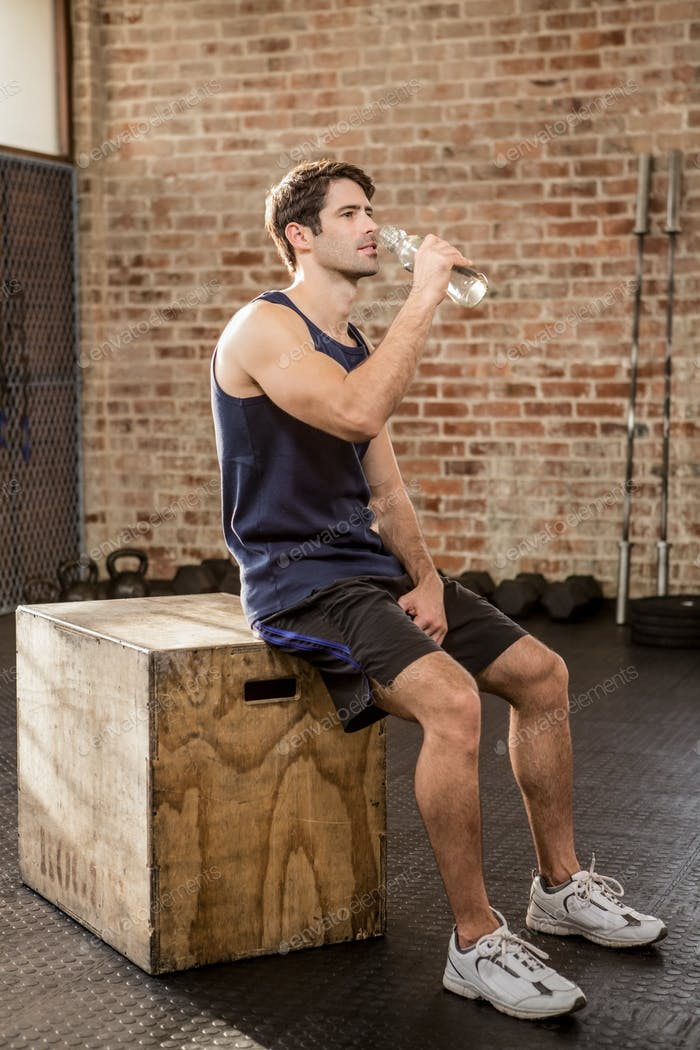 Man sitting on plyo box and drinking water at the gym