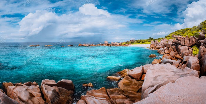 Beautiful panorama with impressive white fluffy clouds wild rocky beach Anse Marron in Seychelles