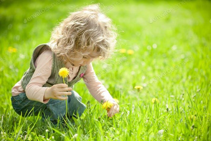 Schönes Kind pflückt Blumen