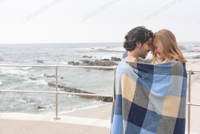 Couple wrapped in blanket standing at promenade near beach om a sunny day