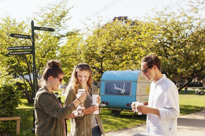 Glückliche Freunde halten Einwegbecher, während sie im Park stehen