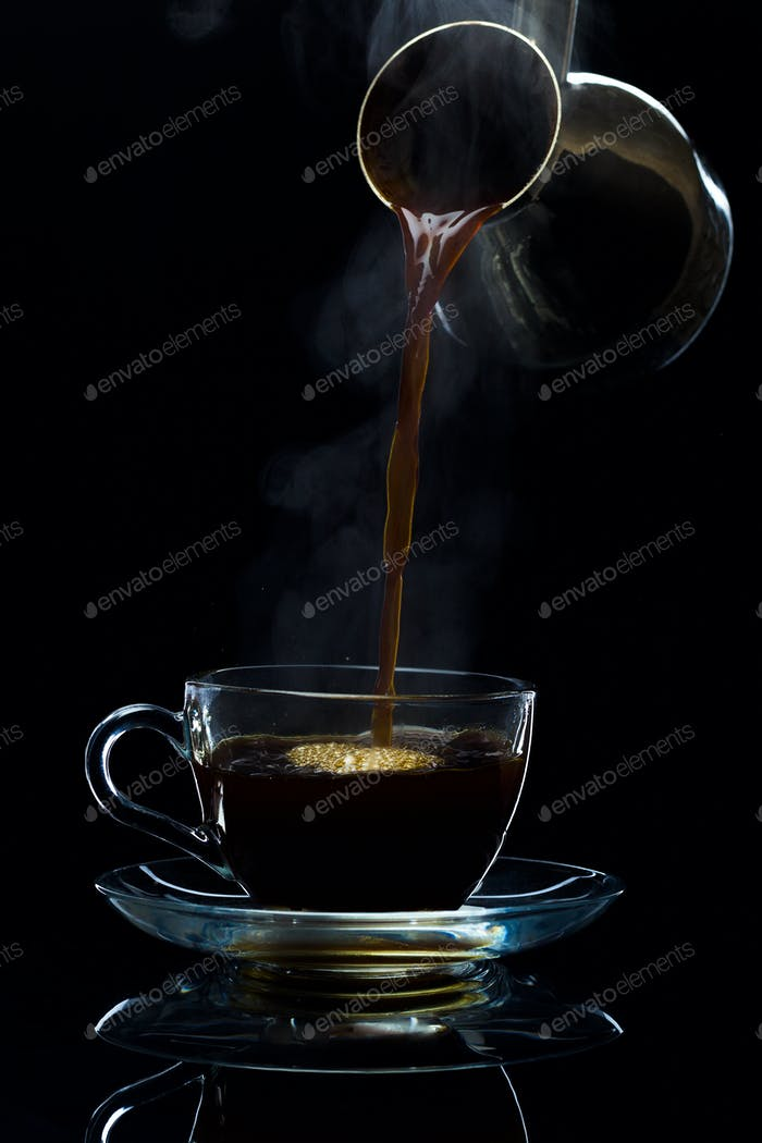 Coffee is poured into a glass cup from the Turks, a black background