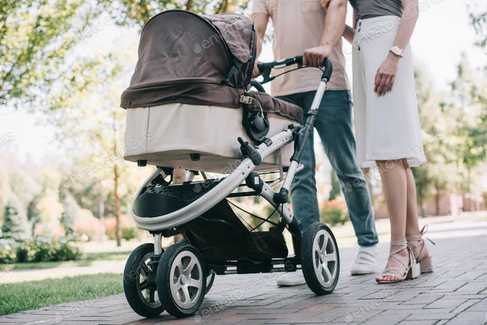 cropped image of mother and father walking with baby carriage in park
