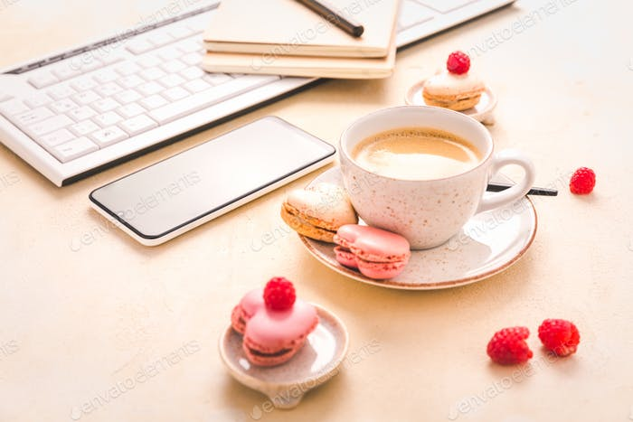 Feminine business workplace with keyboard, writing supplies, cup of coffee and small macarons