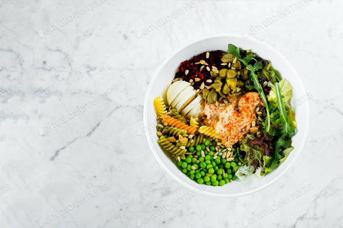 Healthy lunch bowl. Chicken, pasta fusilli, capers, mix greens, vegetables and sunflower seeds