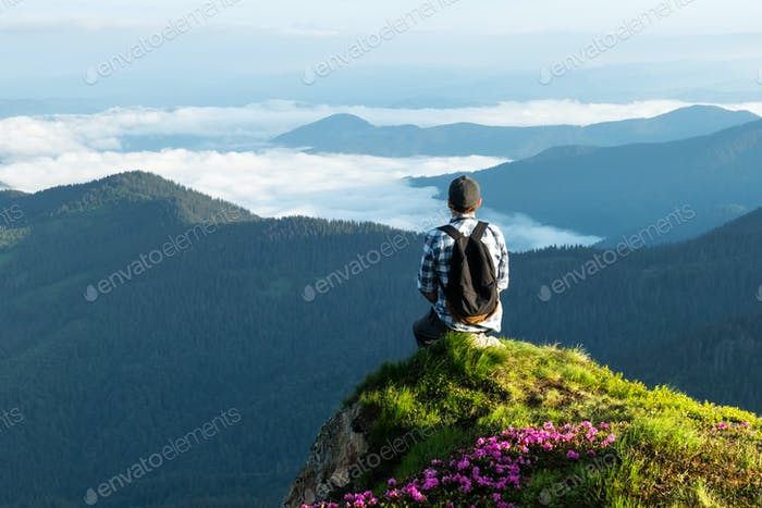 A tourist sits on the edge of a cliff