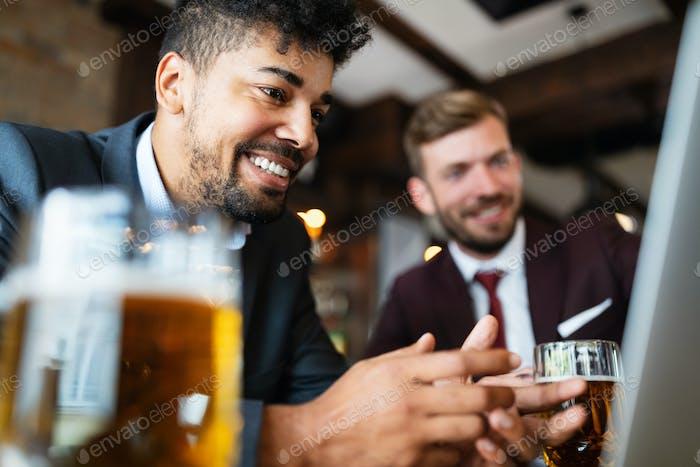 Счастливые молодые бизнесмены в костюмах улыбаются и разговаривают в ресторане