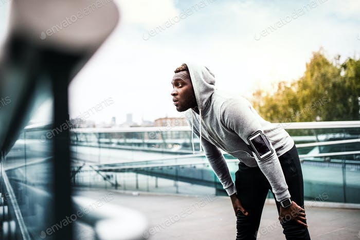 Young sporty black man runner with smartphone on the bridge in a city, resting.