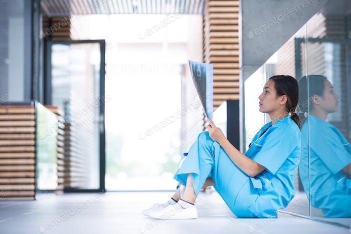 Stressed nurse examining X-ray report