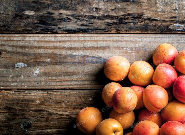 Aprikose. Bio-Früchte mit Blatt auf hölzernem Hintergrund