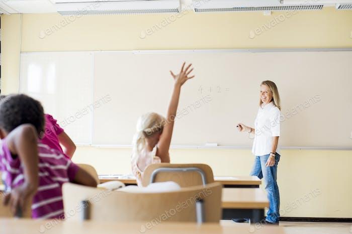 Grundschüler heben Hand in Mathematik Klasse