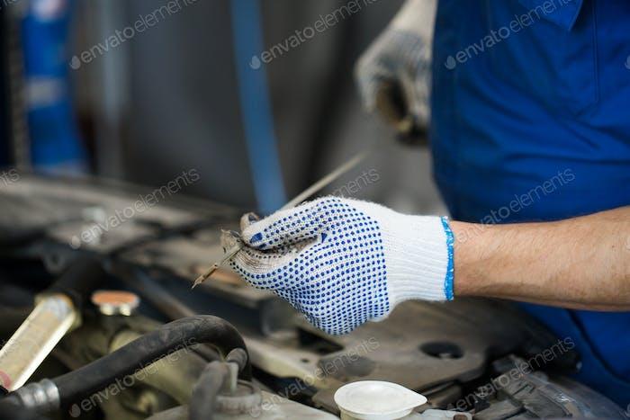 Mechaniker mit Ölmessstab Kontrolle des Motorölstandes