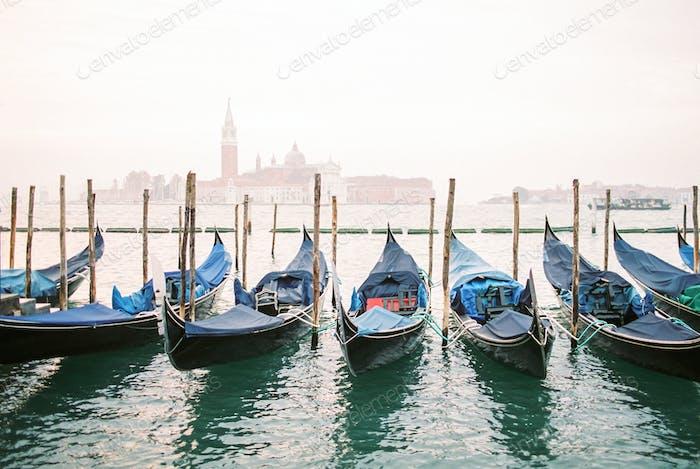 View of Venice lagoon with gondolas and San Giorgio Maggiore on background. Foggy autumn