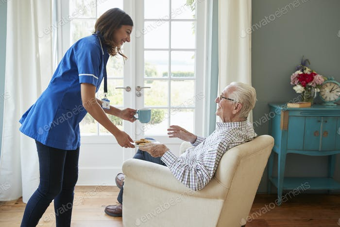 Nurse serving a cup of tea to a senior man at home