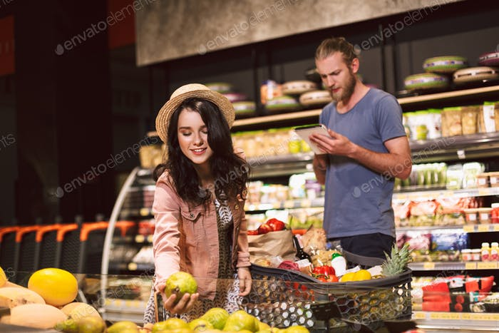 Young serious man thoughtfully reading shopping list while smili