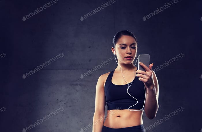 woman with smartphone and earphones in gym