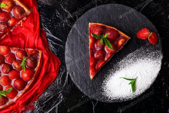 Strawberry pie on black slate plate.