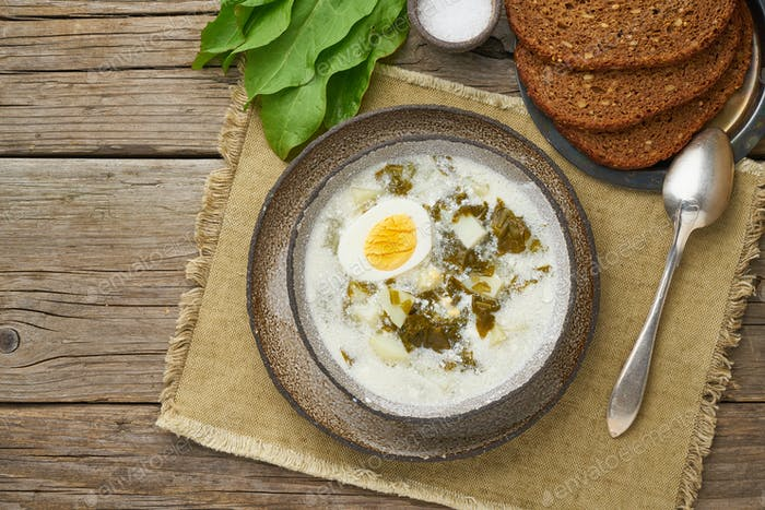 sorrel soup with cream and eggs, wooden background, top view with copy space