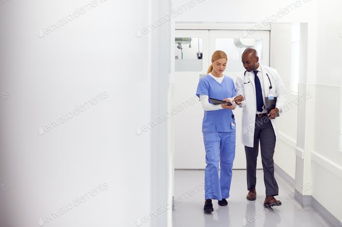 Doctor In White Coat And Nurse In Scrubs Looking At Digital Tablet In Hospital Corridor