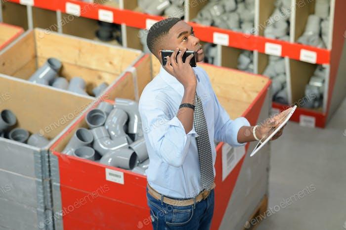 Mann in Rohrverbindungsabteilung, halten Tablette und sprechen am Telefon