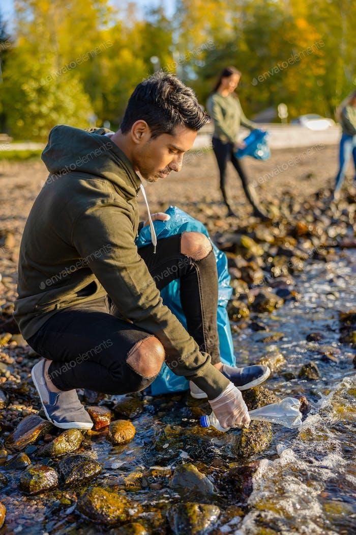 Young volunteer man crouching while picking up garbage on shore