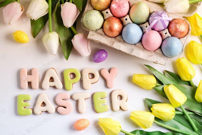 Oster-Grußkarte mit Tulpenblüten Muster, Ostereier und Kaninchenkekse Draufsicht über weiß