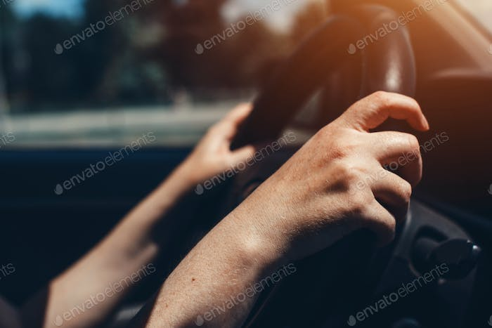Female hands on car steering wheel