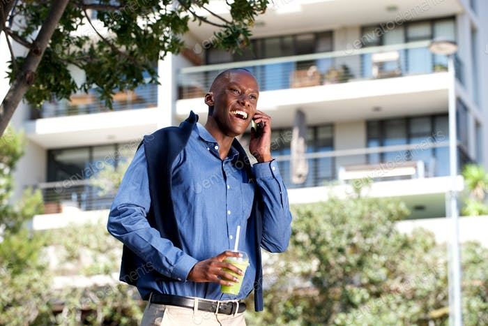 happy black guy walking and talking on cellphone outdoors