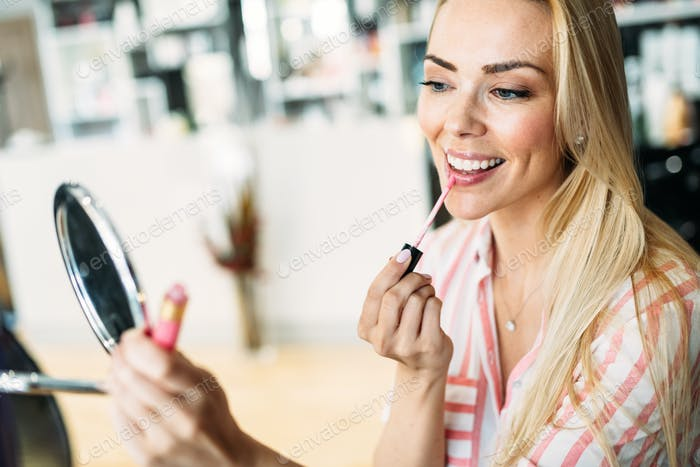 Young beautiful woman applying make up using small mirror