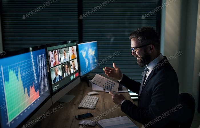 Businessman with computer sitting at desk, working late. Business call concept
