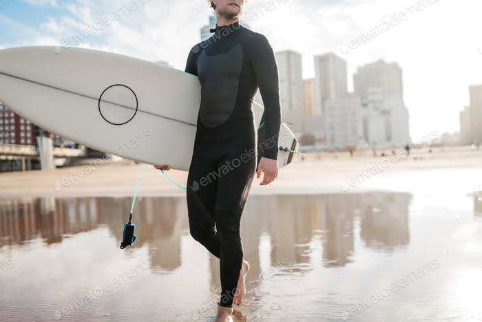 Surfer entering into the water with his surfboard.