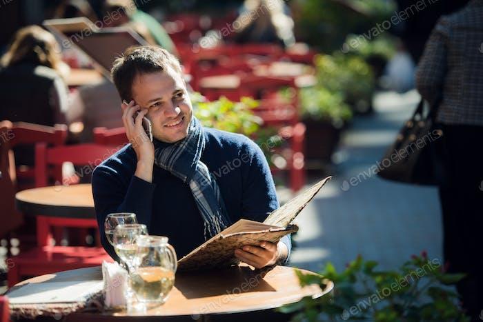 Mann im Café mit Smartphone reden und bestellen etwas. gut aussehend junge casual Kerl mit Handy