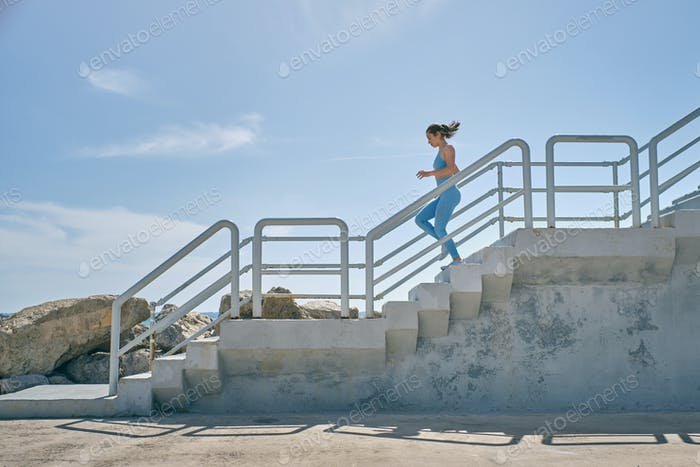 Runner jogging on staircase during workout in sunlight