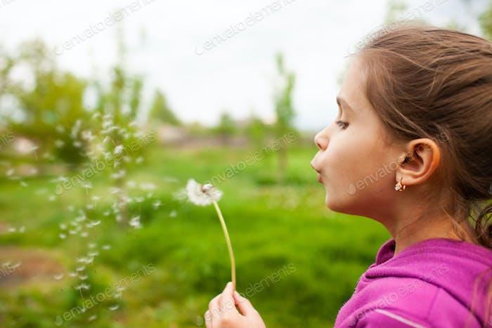 Little beautiful girl holds spring dandelion in her hand